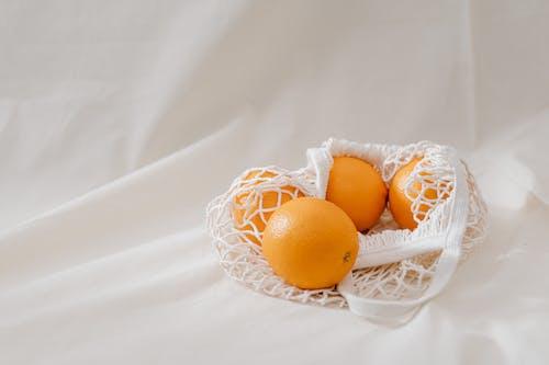Four  Orange Fruits on White Textile