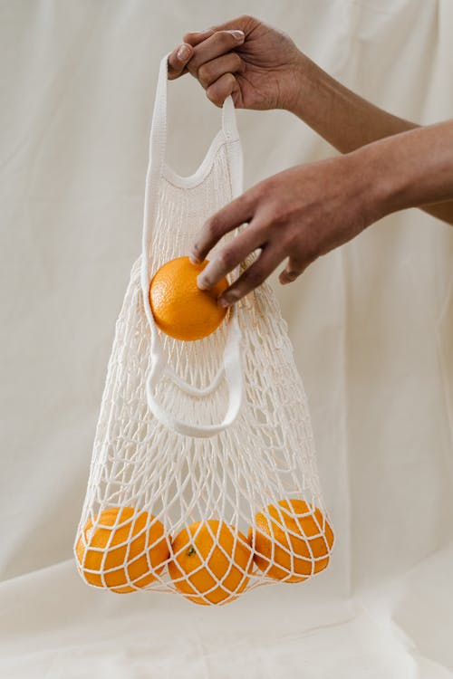 Person Holding Orange Fruits in White Net