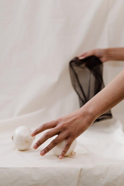 Person Holding White Onion on White Textile