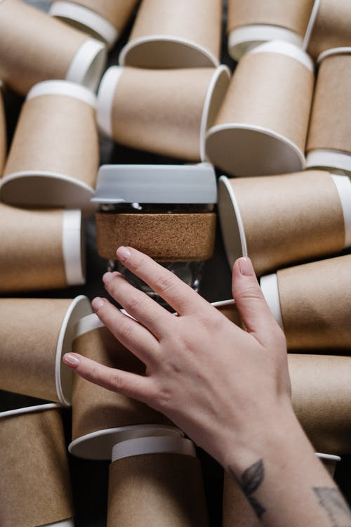 Person Holding Brown And White Paper Cups