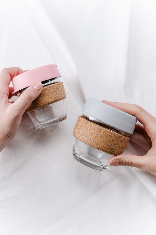 Person Holding Pink and Brown Plastic Containers