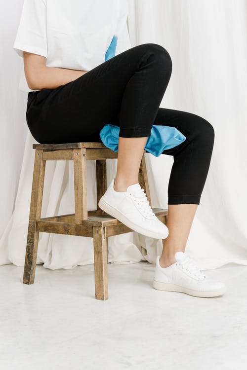 Person in Black Leggings and White Sneakers Sitting on Brown Wooden Stool