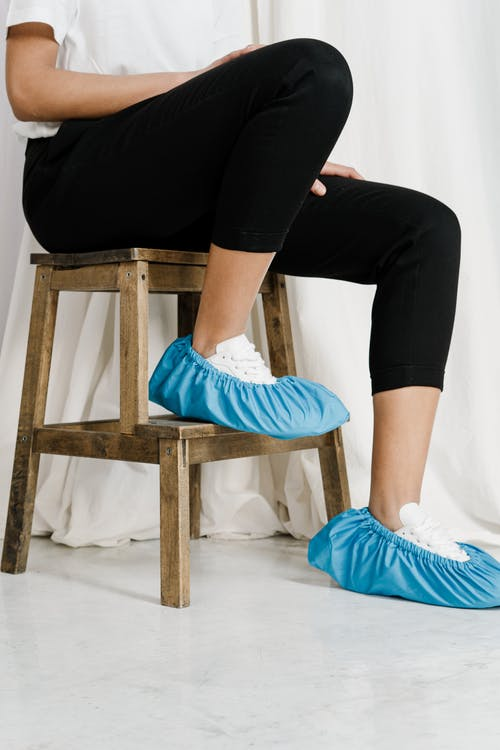 Person in Black Pants Sitting on Brown Wooden Stool