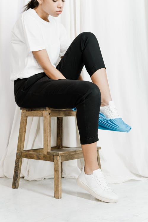 Woman in White T-shirt and Black Pants Sitting on Brown Wooden Stool