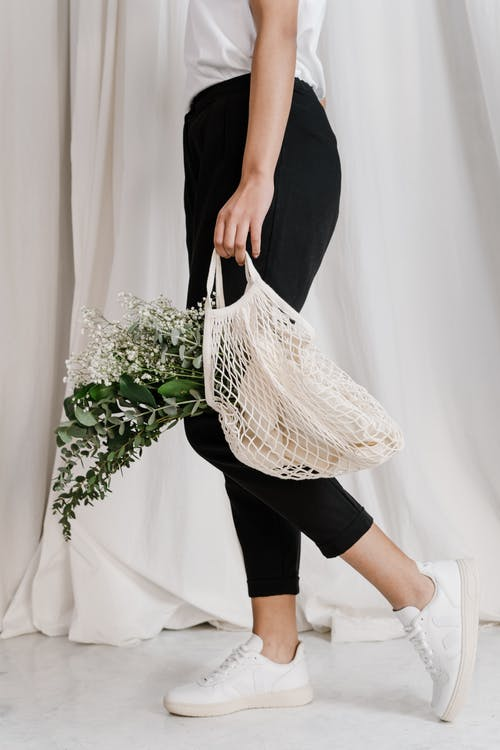 Woman In Black Pants Holding Net Bag