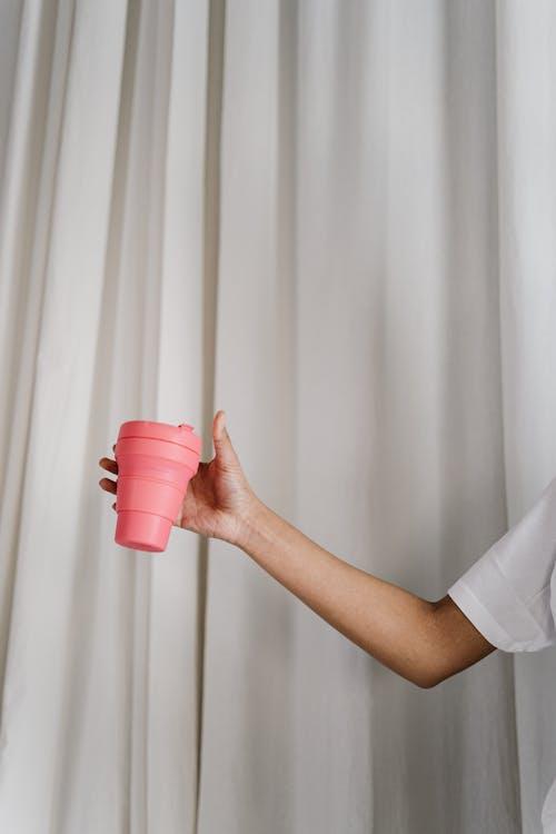 持有粉紅色塑料杯的人