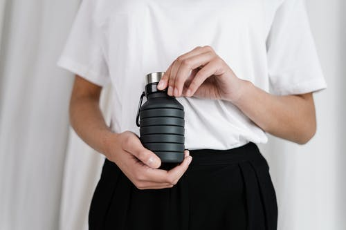 Person In White Shirt Holding Black Rubber Bottle