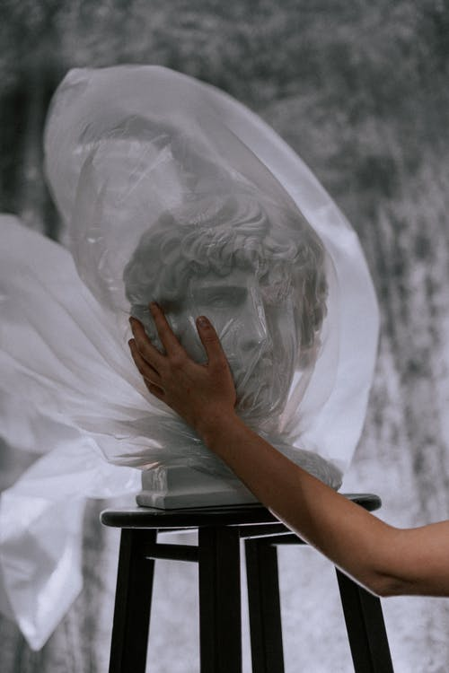 Person Holding Gypsum Head Covered With Plastic Bag