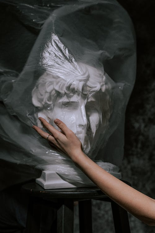 Person Holding Gypsum Head With White Plastic Bag