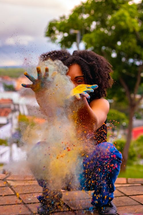 Anonymous African American female squatting on tile pavement with hands apart while playing with multicolored dry paints during Hindu Festival of Colors under cloudy sky