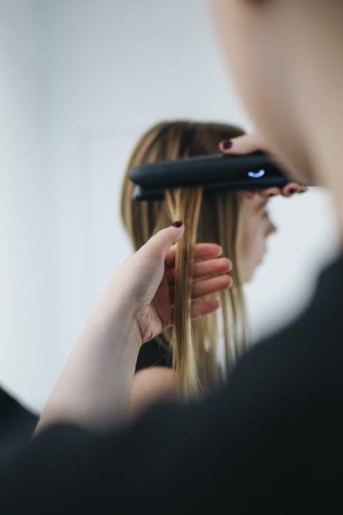 Selective Focus Photo of Person Ironing a Woman's Hair