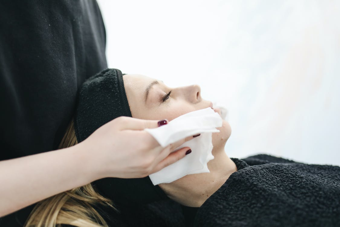Photo of Person Using a Tissue to Dry a Woman's Face