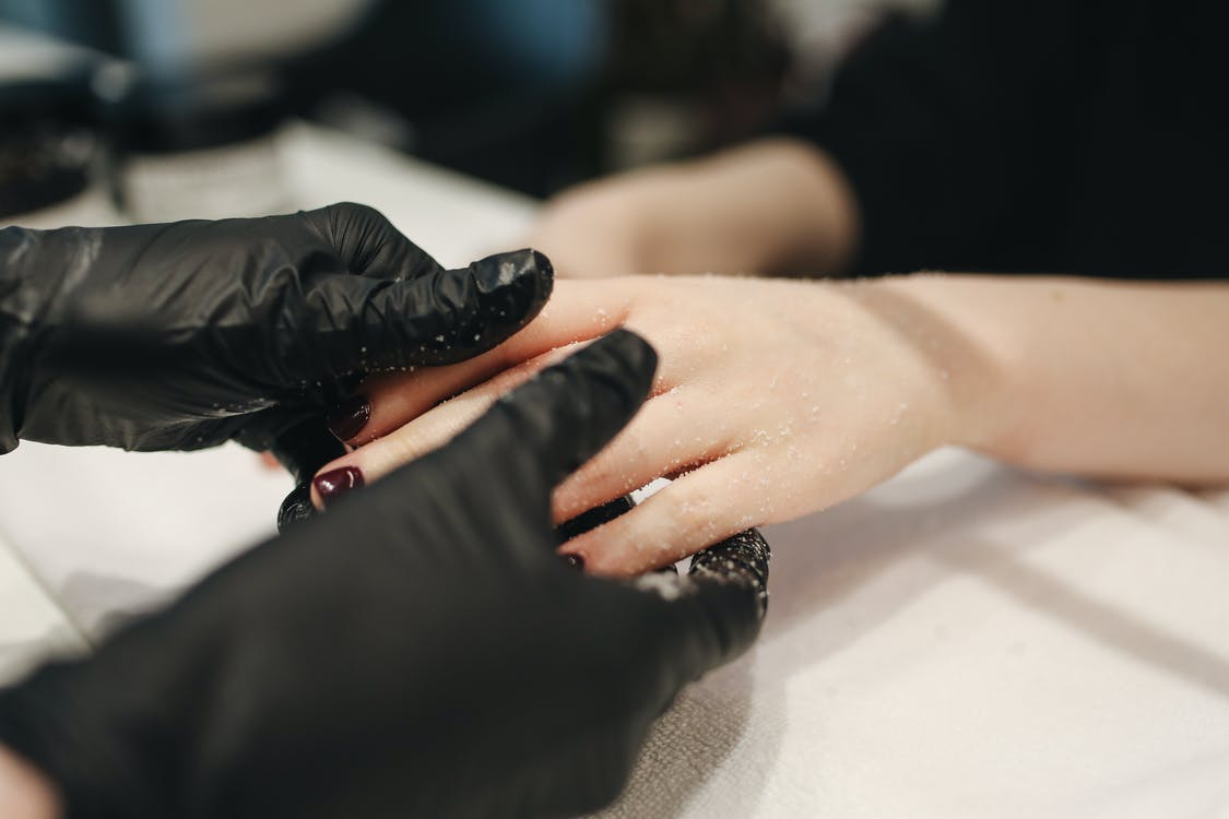 Person Wearing Black Gloves Massaging a Person's Hand