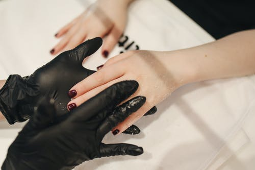 Person's Hand Wearing Black Gloves