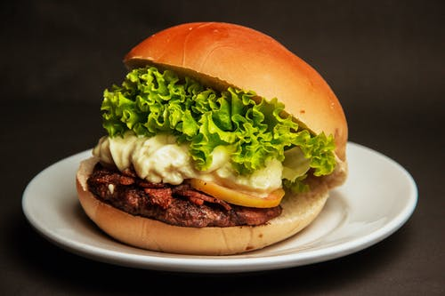 Burger With Lettuce and Cheese on a White Plate