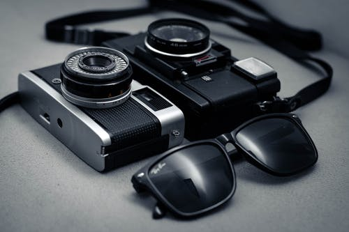 Black And Silver Camera Beside Black Sunglasses