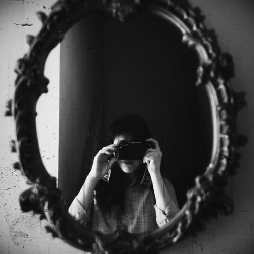 Grayscale Photo of Woman Taking Photo of Round Mirror