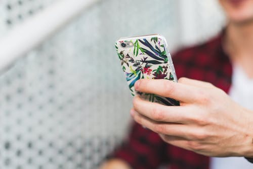 Person Holding Smartphone With White and Green Floral Case