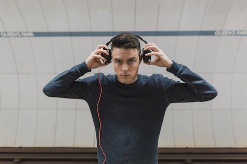 Man Putting His Headphones on His Ears
