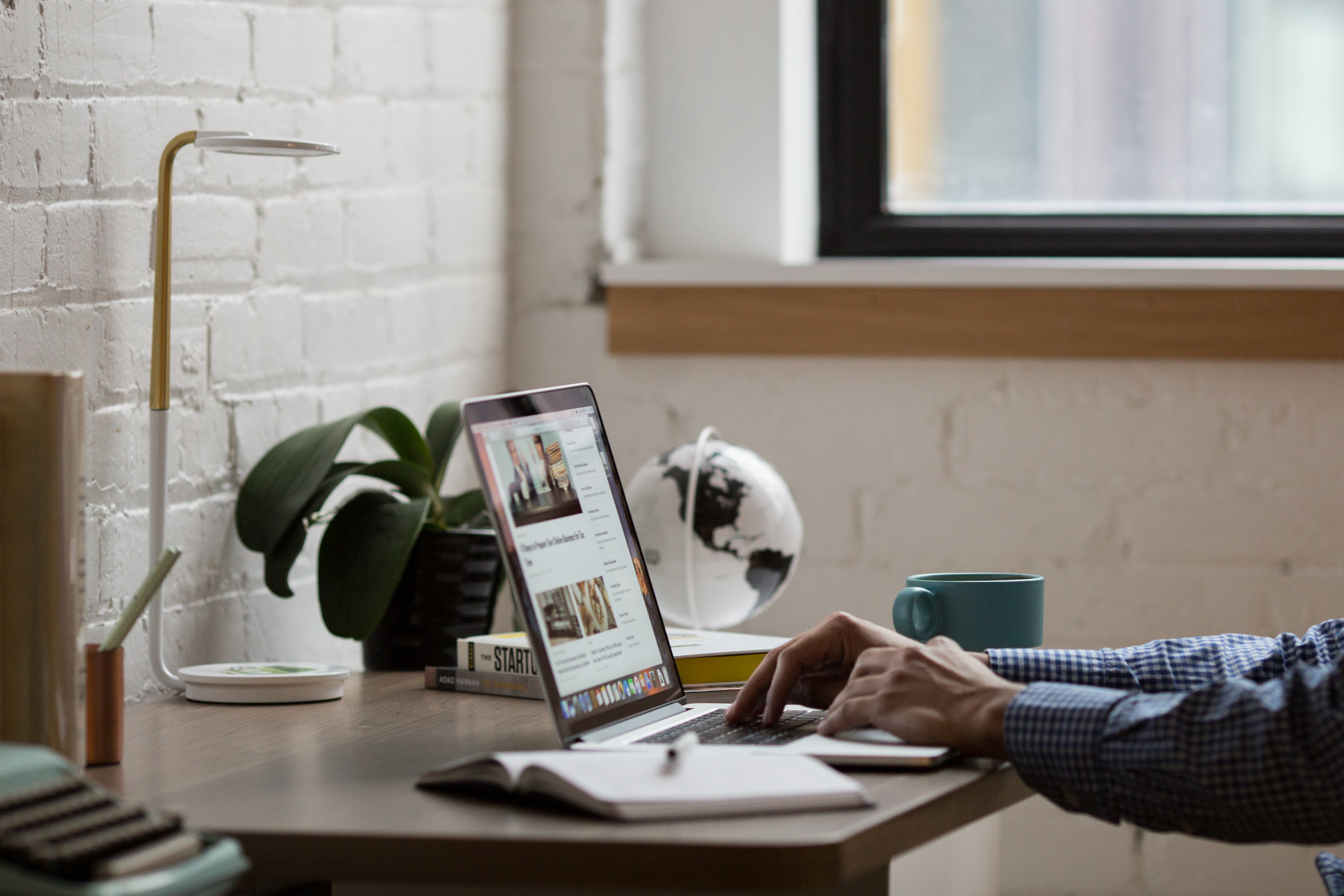 Man Sitting in Front of Turned-on Laptop on Brown Wooden Desk