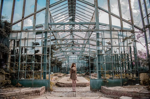 Unrecognizable woman standing near old metal construction under cloudy sky