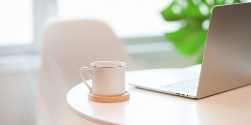 Photo of White Cup Near Laptop