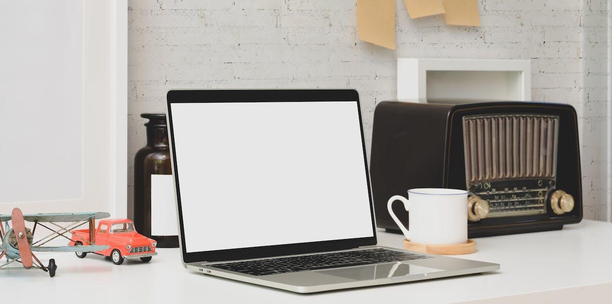Macbook Pro Beside White Ceramic Mug on White Table