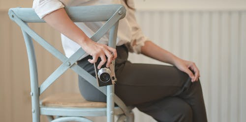 Crop photographer taking photo on camera sitting on old stool
