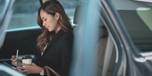 Woman in Black Blazer Sitting on Car Seat Using Tablet Computer