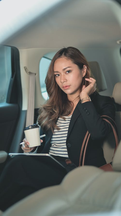 Asian designer with coffee and graphics tablet inside car