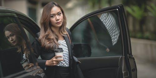 Woman in Black Blazer Standing Beside a Car