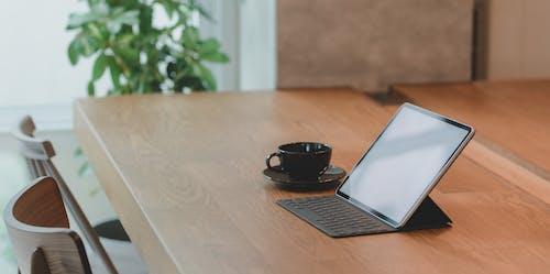 Black Ceramic Cup Beside Black Tablet Computer