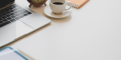 White desk with netbook and coffee placed near notepad and clock in daytime