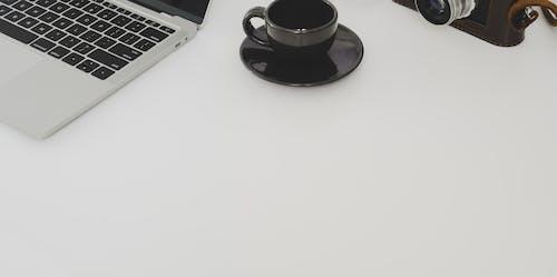 Black Ceramic Cup on Saucer Beside Laptop Computer