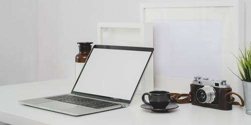 Black and Silver Laptop Computer Beside Black Ceramic Cup on White Table
