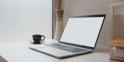 Laptop Computer Beside Black Ceramic Cup on White Table