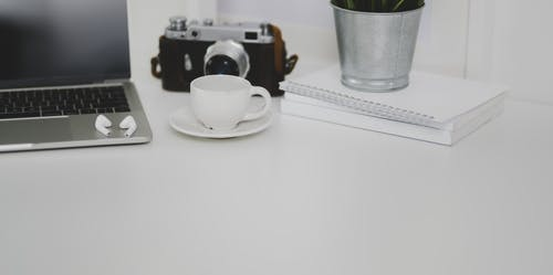 White Ceramic Cup on Saucer Beside Laptop Computer