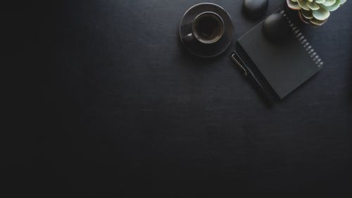 Black Ceramic Cup Beside Notebook on Black Surface