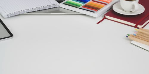 Colorful pencils and notepads laced on white desk with coffee cup