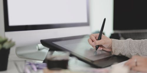 Unrecognizable graphic designer using tablet in office