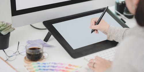 Woman sitting at desk drawing on graphic tablet