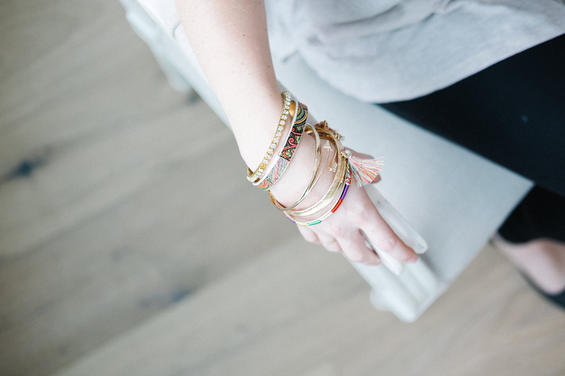 Selective Focus Photo of Person's Hand With Gold-bangles