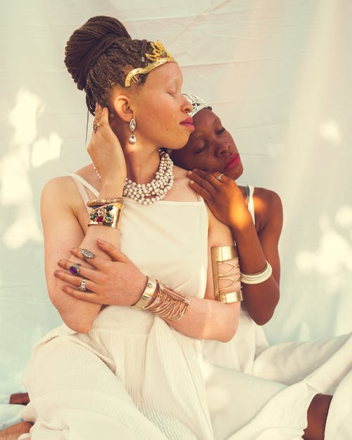 Woman Hugging Woman in White Dress and Golden Crown