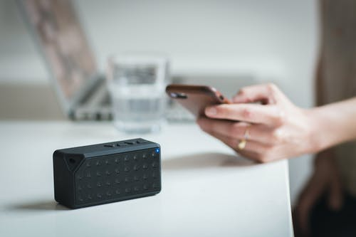 Person Holding Iphone Beside Black Portable Speaker