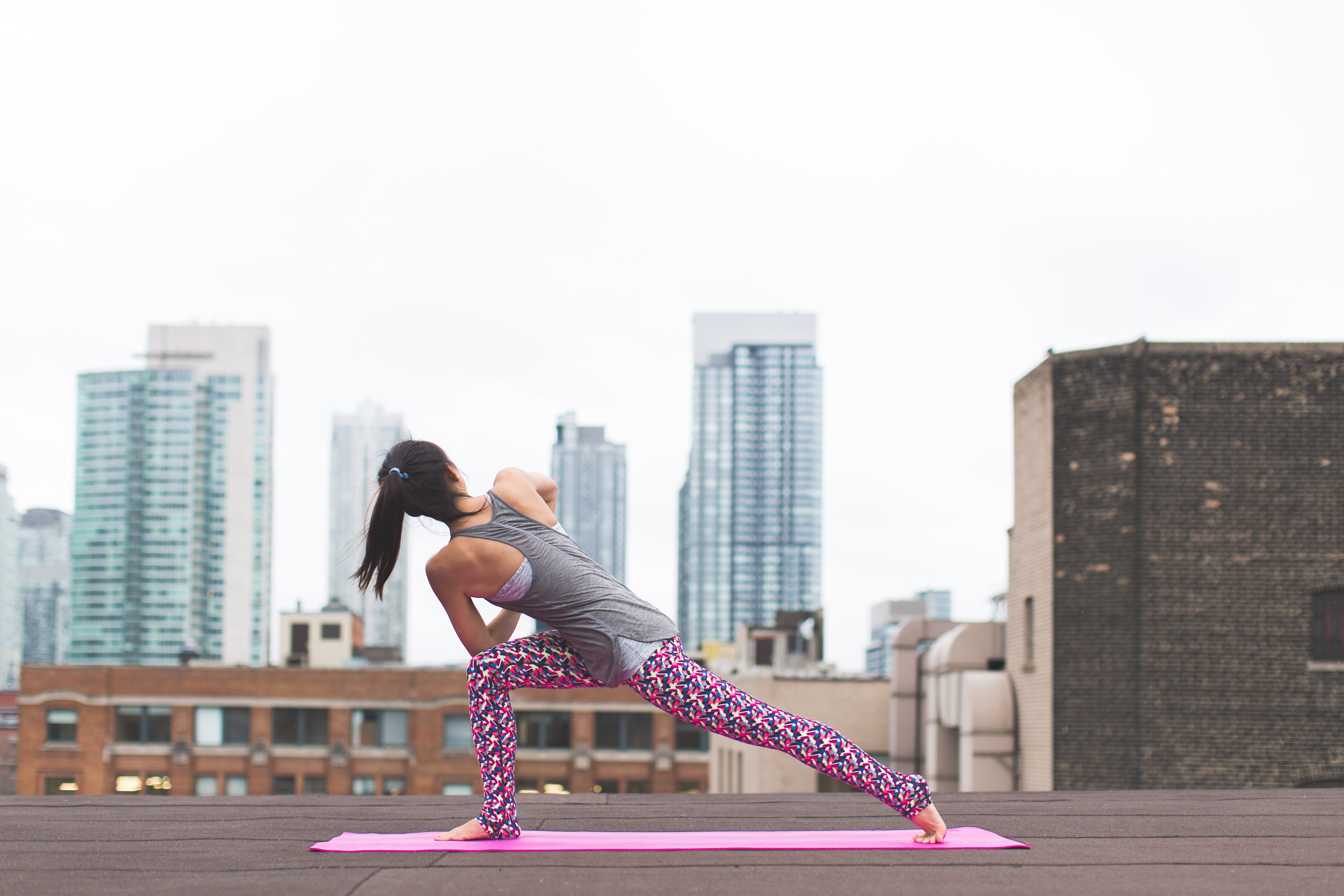 Woman Standing on Pink Yoga Mat Stretching