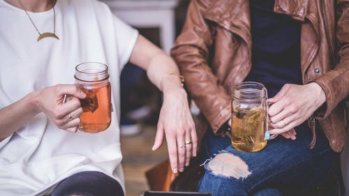 Two Person Holding Clear Glass Mugs Sitting