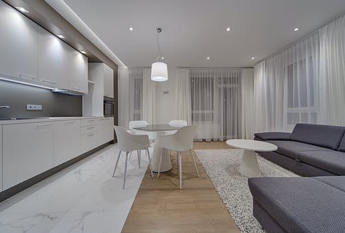 Minimalist modern design of kitchen with white cabinets and gray sofa in contemporary illumination