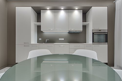 Design of kitchen with white cabinets and contemporary appliances with glass table and white chairs in apartment