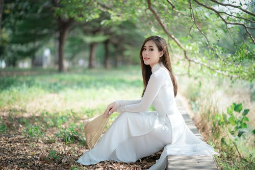 Elegant woman in vintage clothes sitting in park