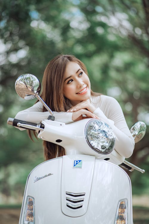 Happy ethnic model leaning on handlebar of retro motorcycle and looking dreamily away in woods